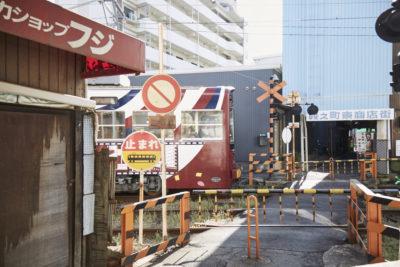 昭和レトロな商店街を横断する路面電車を眺める
